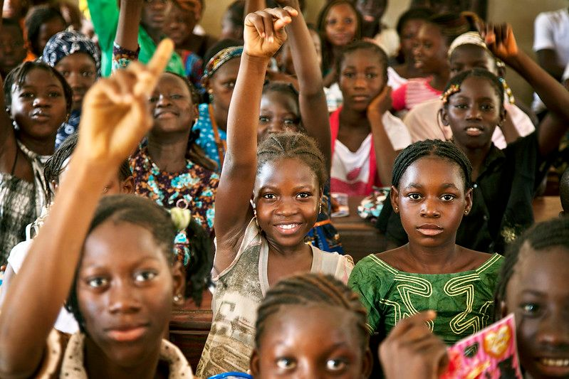 Young girls raise their hands in class