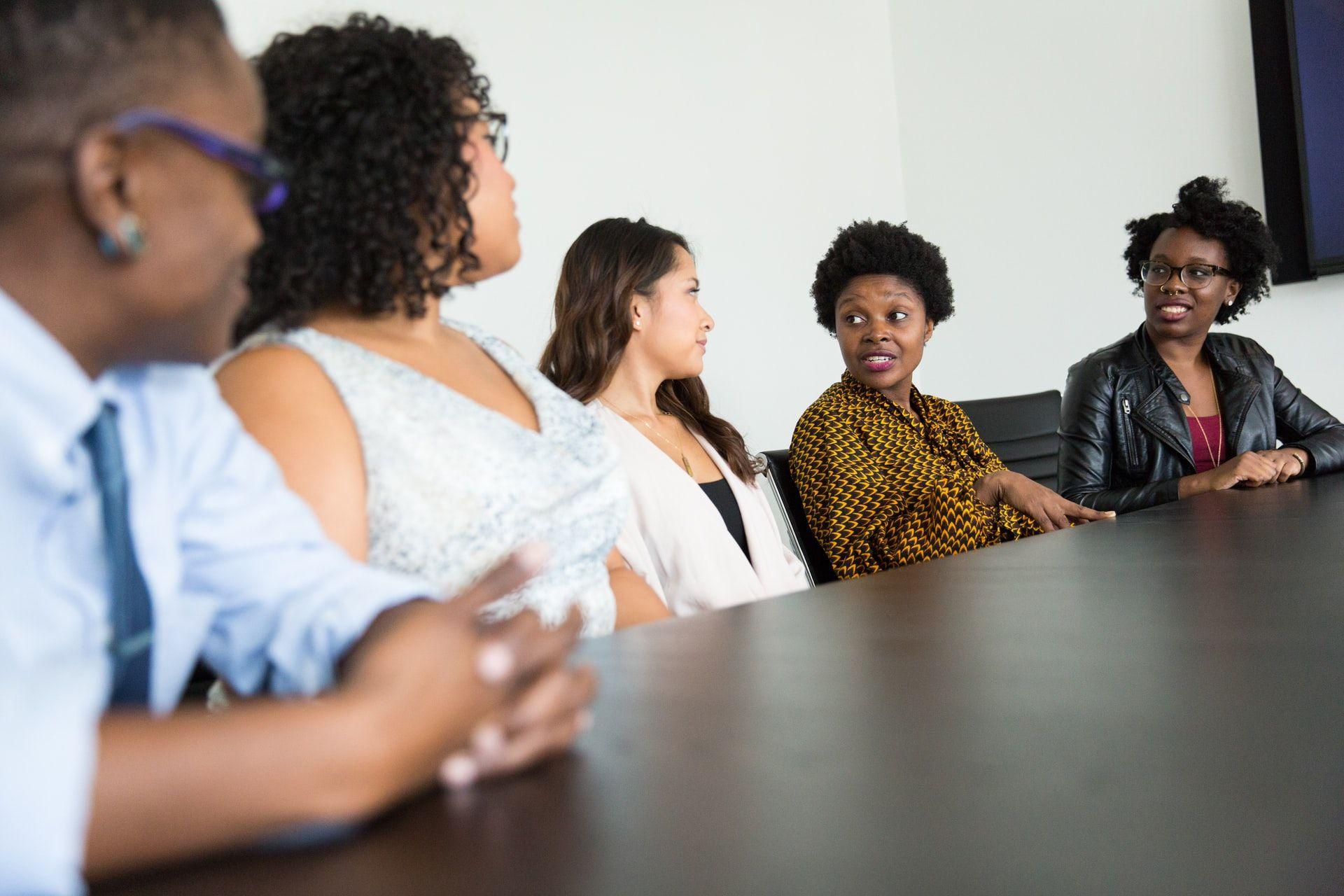 Diverse group of women around a working desk talking