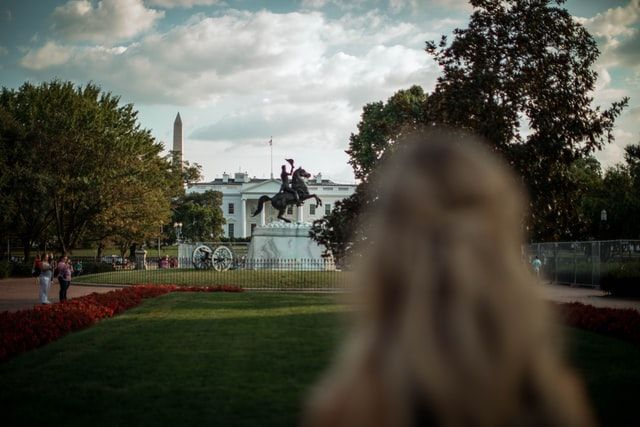 Silhouette of woman looking at the White House in the back. Photo by Roberto Nickson on Unsplash.