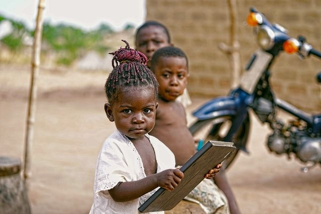 Girl holding a tablet in Nigeria. Photo by Victor Nnakwe on Unsplash.