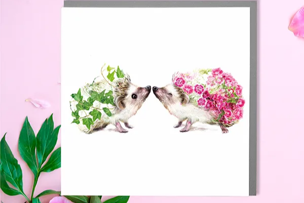 two hedgehogs with flowers on a greeting card lola design