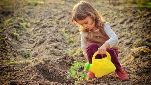 Baby watering plants