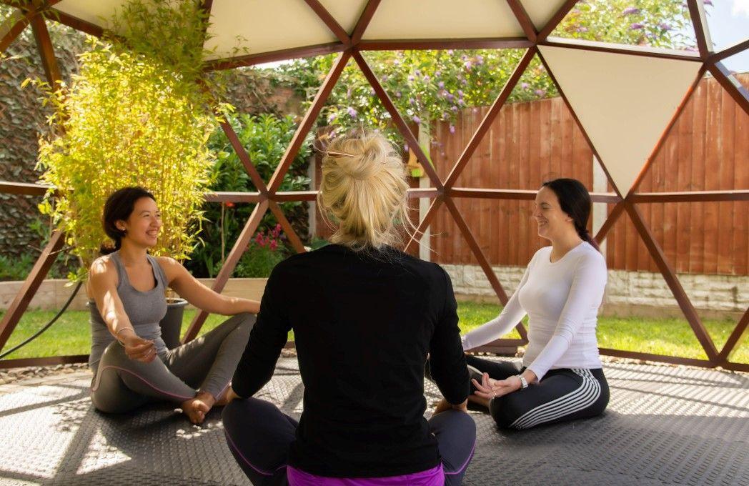 3 women doing yoga under dome in garden