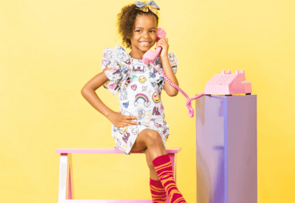 Little girl talking on a pink telephone