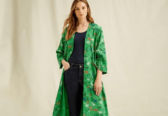 Woman standing wearing a green kimono with palm tree print