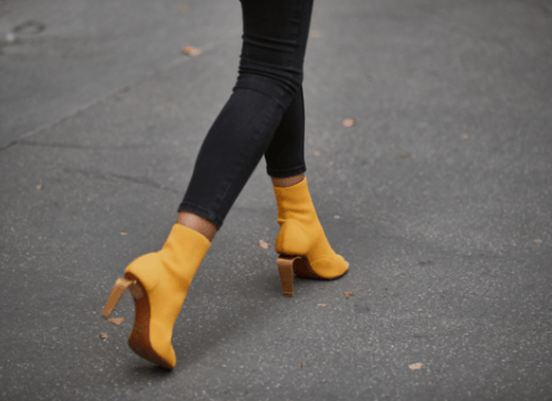 Yellow high-heeled boots walking on road