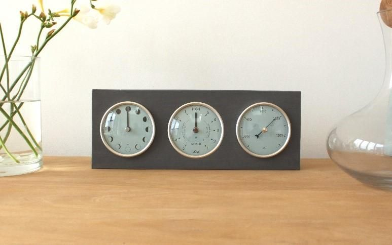 three dial clock on table