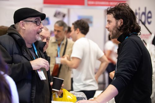 Mid-way Conversation of Male Visitor and Male Exhibitor