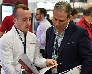 Attendee and exhibitor looking at a brochure at Franchise Expo