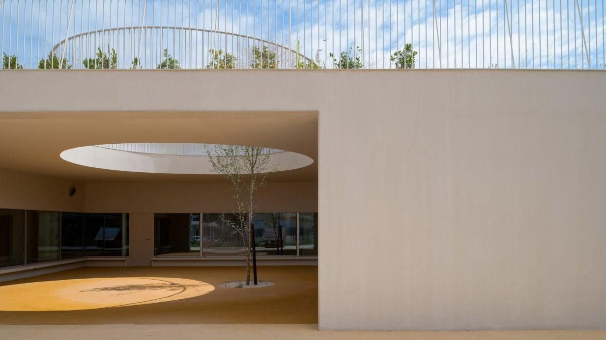 Circular holes connect playgrounds on two levels of a Lisbon school
