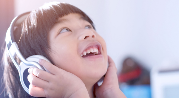 Child smile whilst listening to music with headphones on.