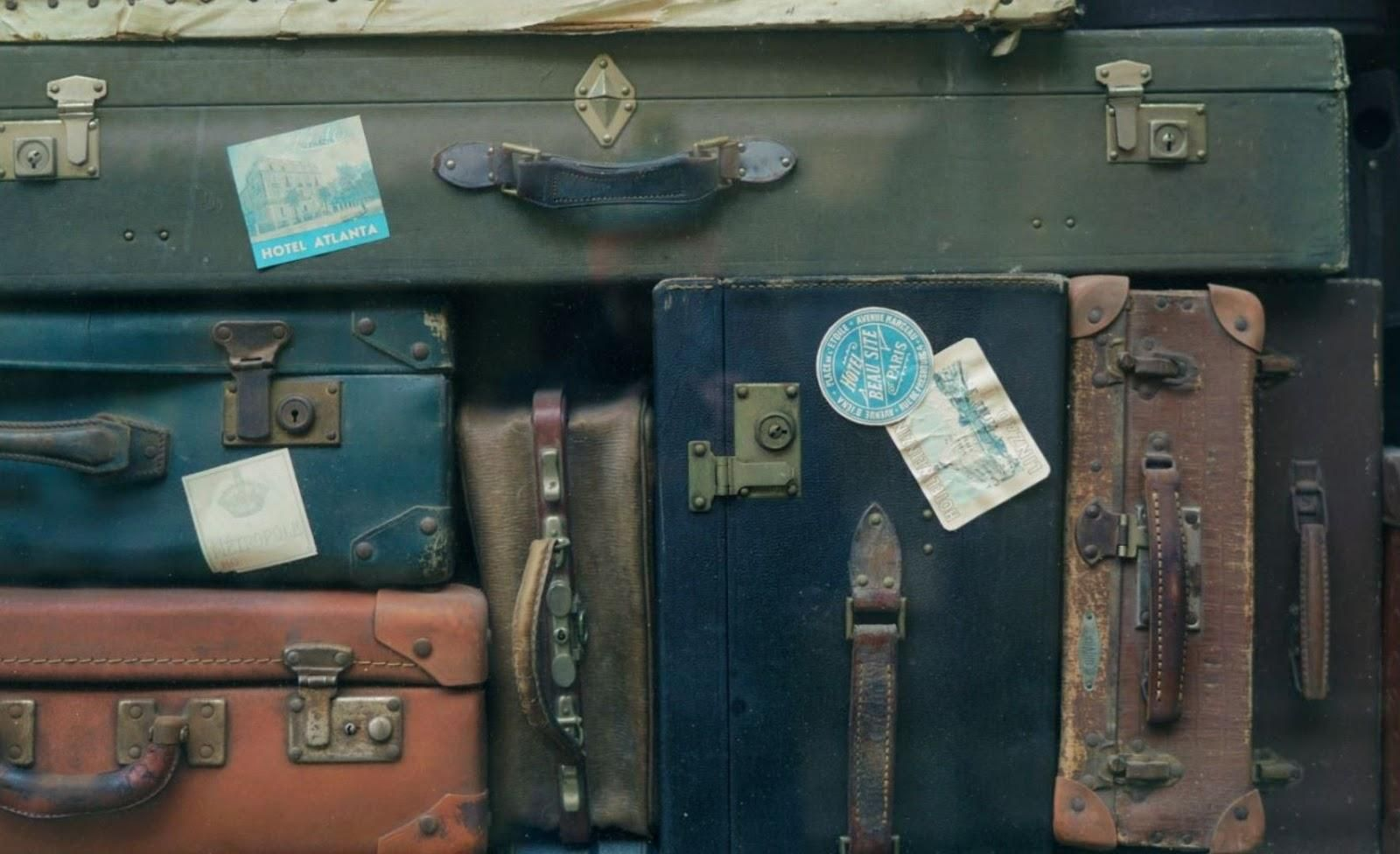 Picture of a range of different old suitcases.