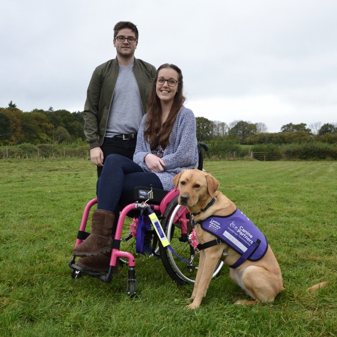 Picture of a man standing and a lady using a wheelchair, looking happy with their dog by their side.