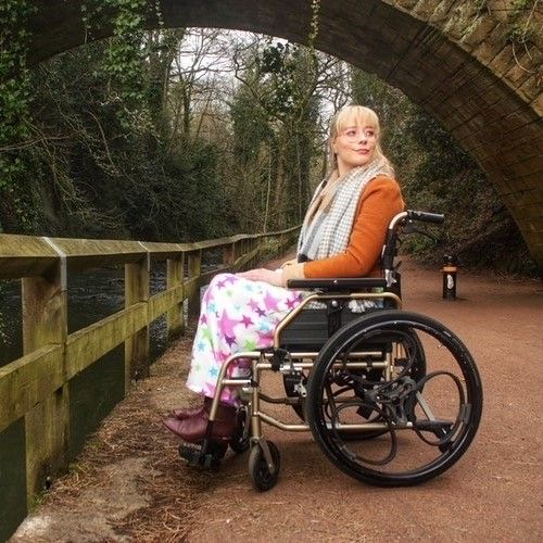 Picture of a woman using a wheelchair. She is by a river looking thoughtful.