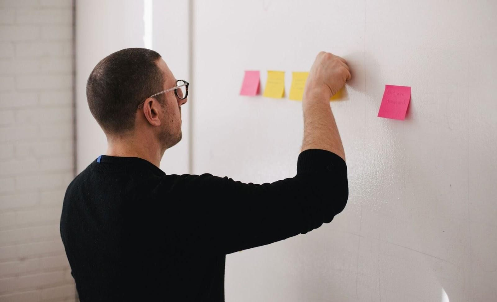 Picture of man sticking sticky notes on a wall