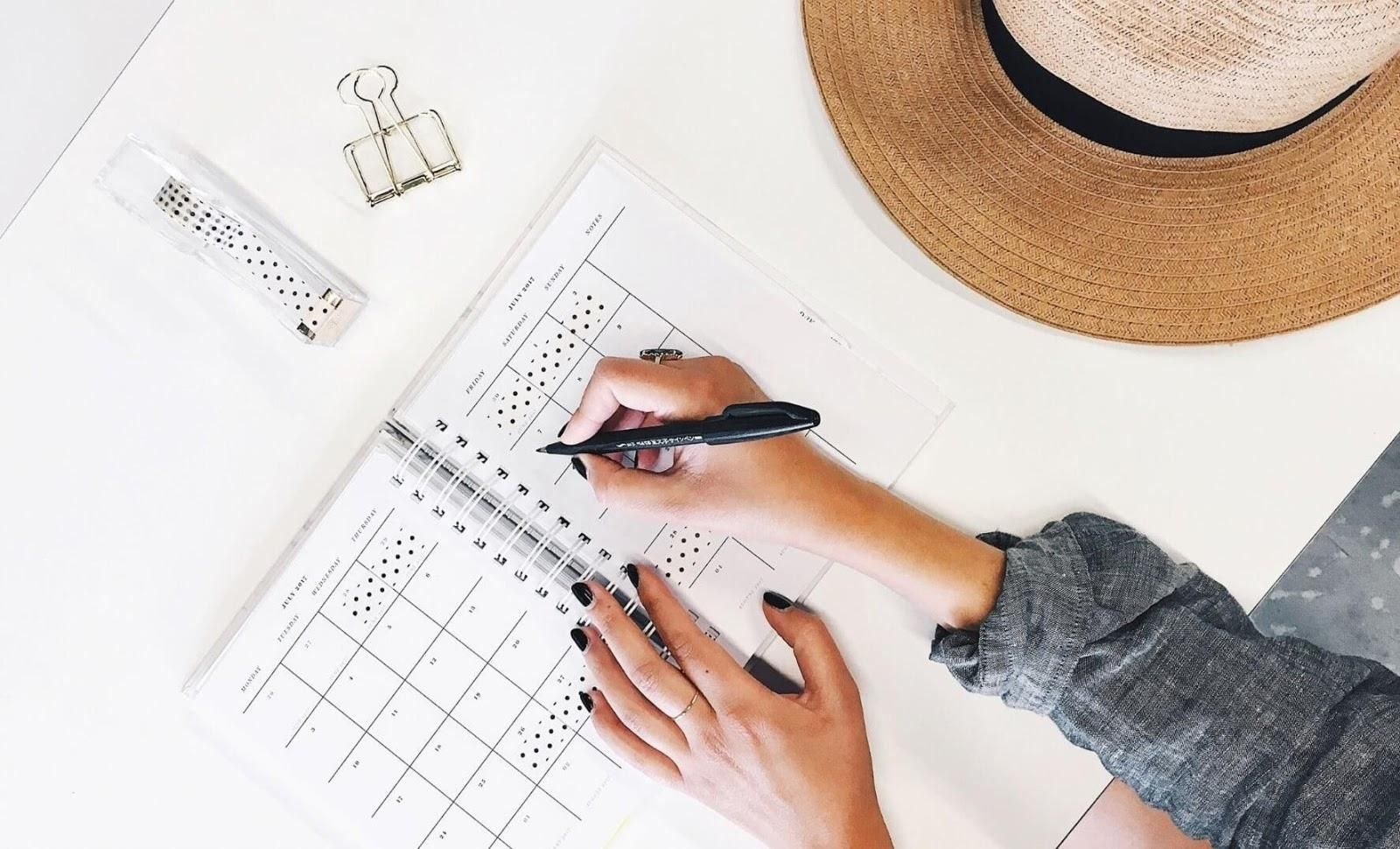 Image of a person taking notes on a diary planner