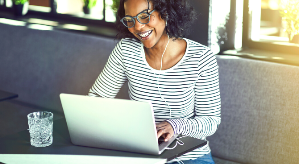 Picture of lady using a laptop and smiling.