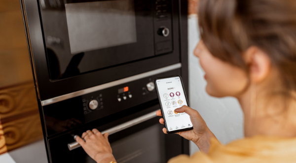 Picture of a lady using a smart oven.